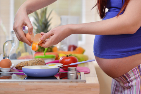 Pregnant woman cracking an egg in a pan