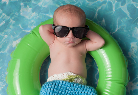 baby in sunglasses on rubber ring in pool