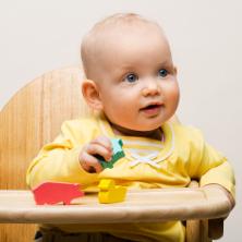 baby in wooden highchair