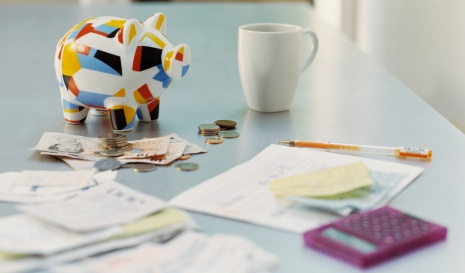 An image of a piggy bank, money and calculator on a table