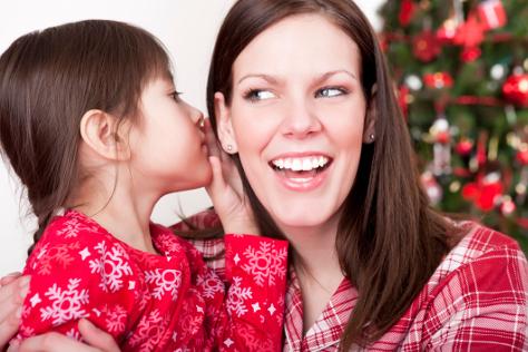 Child whispering to mum at christmas