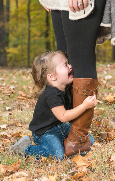 Toddler holding on to mums legs crying