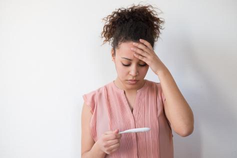 Woman looking worried at pregnancy test