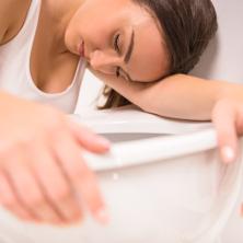 Woman feeling sick leaning on toilet
