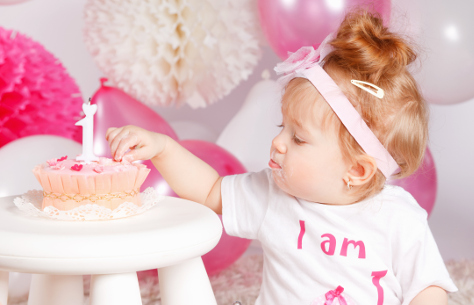 One year old girl eating her birthday cake