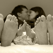 couple in bed with newborn