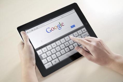 Woman typing in Google on iPad