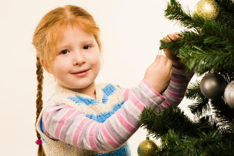 Young girl decorating Christmas tree