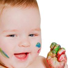 A baby playing with fingerpaint