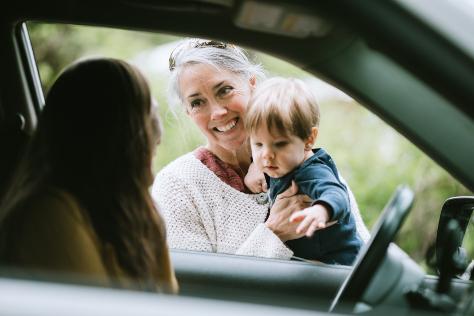 Mum in car grandparent and baby waving
