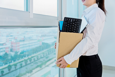 Woman carrying box of office belongings