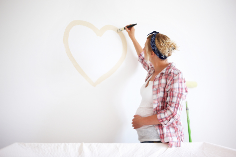 Pregnant woman painting wall